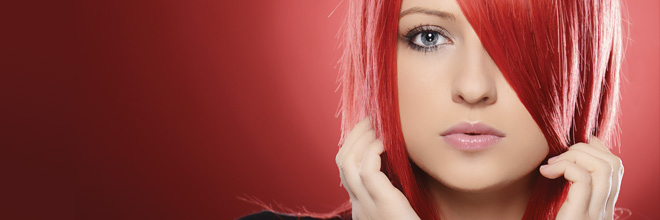 Woman with red hair standing in front of red background